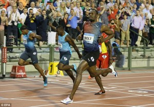 Usain Bolt (right) easing to victory today.