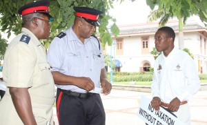 Students Guild President, Damanni Parris in discussion with Acting Assistant Superintendent of Police, Anderson Bowen (middle) and Inspector Peter Gibson in Jubilee Gardens this morning.