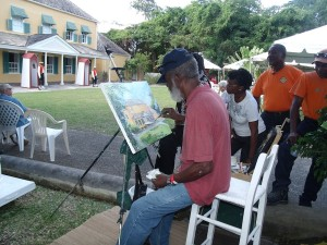 Barbados renowned artist, Fielding Babb, captures the attention of onlookers as he puts together a work of art in the courtyard of George Washington House. In the foreground are two sentries at their posts awaiting the ceremonial changing of the Sentry.