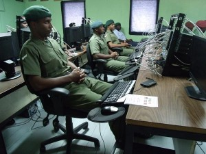 Some graduates of the data communication course  at their workstations during the graduation ceremony. Inset, Lance Corporal Curtis Davidson of the Trinidad  and Tobago Defence Force delivering the vote of thanks at the graduation ceremony.