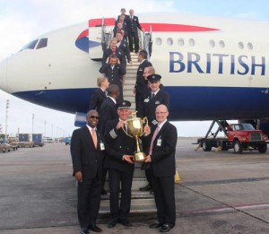 Minister of Sport Stephen Lashley (left) and Captain Paul Owens (second left) hold the Gold Cup after it arrived today on a British Airways flight.