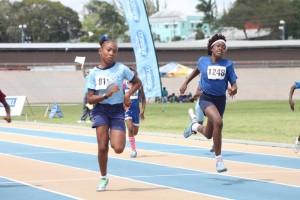 Sumara Benn wins the U-13 100m ahead of St. Martin Mangrove's Akera Pollard.