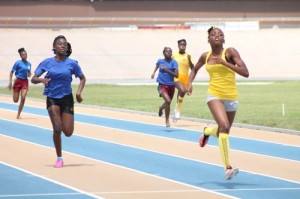 Yellow House's Kayla Walters pulling away from the field in the under-15 girls' 200m, while chased by Takara Bryan of Blue House.