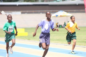 Zavion Nurse of St Philip's Primary fighting to victory ahead of St Catherine's Primary's Todd Miller and Vishaul Chase of St Bernard's in the U-13 400 metres.