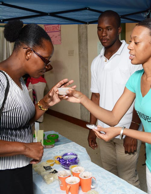 A student showing a parent one of the natural body products she made.