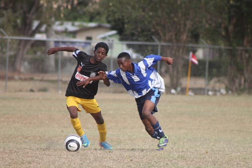 Foundation's Elijah Donney (left) trying to clear the ball under the challenge of Alexandra's Trisquon Connell during their third-place play-off game.