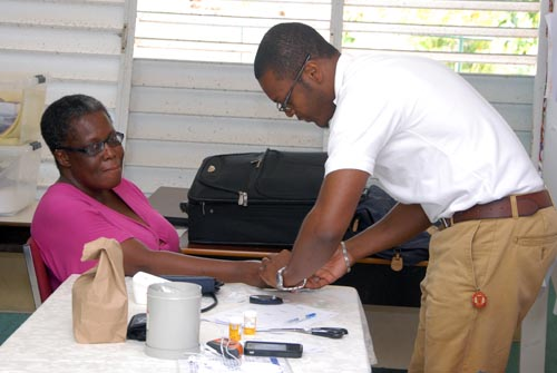 A parent getting her blood pressure checked by one  of the Knights Advantage Health Club representatives.
