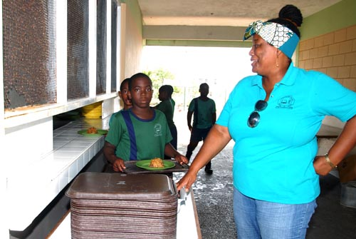 Teacher Cherryann Layne looks on as some of the Class 2 children collect their lunch.