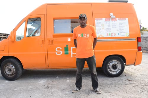 Creative director of Sips Smoothie Bar, Corey McClean, posing beside his mobile business, which has been in operation since December 2008.