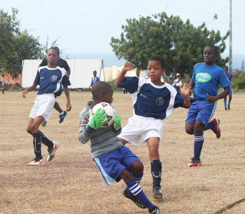 St Bartholomew's goalkeeper Rick-Kobe Lewis held on to a good save with Wills Primary striker Zion Mayers charging in.