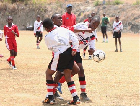 St Stephen's goal scorer Victor Obiora is sandwiched between two Sharon Primary defenders.