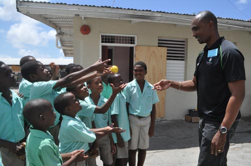 Father Gregory Brathwaite (right) teaching students how to play catch.