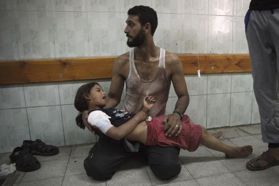 A Palestinian man holds a girl, whom medics said was injured in an Israeli shelling at a U.N-run school sheltering Palestinian refugees, at a hospital in the northern Gaza Strip