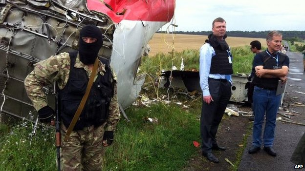 OSCE monitors (right) reach the crash site, escorted by rebels