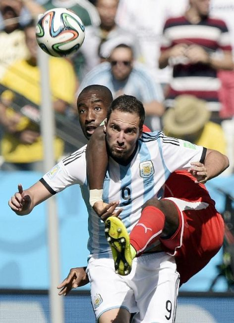 Switzerland's defender Johan Djourou (L) and Argentina's forward Gonzalo Higuain (front) vie for the ball during a Round of 16 football match between Argentina and Switzerland at Corinthians Arena in Sao Paulo during the 2014 FIFA World Cup on July 1, 2014.     (AFP PHOTO / NELSON ALMEIDAJUAN MABROMATA/AFP/Getty Images)