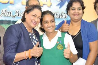 TWO THUMBS UP- Top SEA pupil, Shivanna Chatoor, is hugged by Prime Minister Kamla Persad-Bissessar at the Avocat Vedic Primary School, Fyzabad, yesterday. At right is her mother, Gaitree Chatoor.