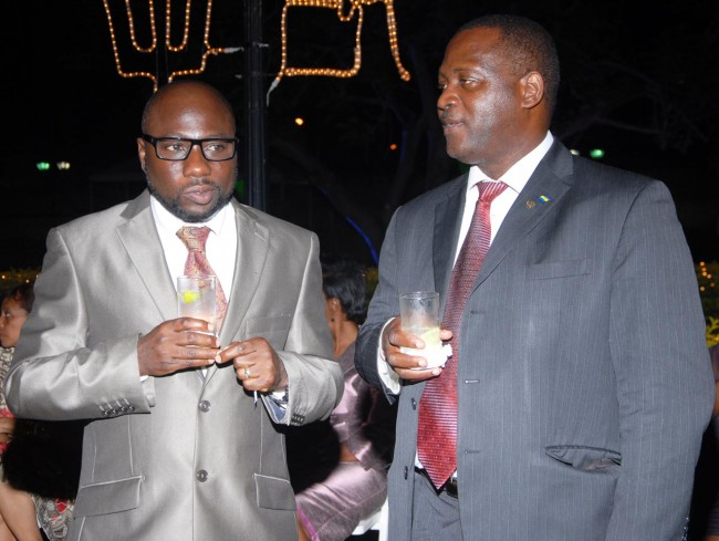 St George South MP Dwight Sutherland (left) and Minister of Commerce Donville Inniss sert aside the political divide last night.