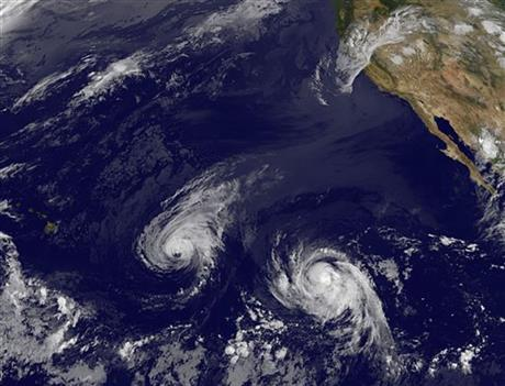 This image provided by NOAA taken Wednesday Aug. 6, 2014 shows Hurricane Iselle, center, and Hurricane Julio, right.