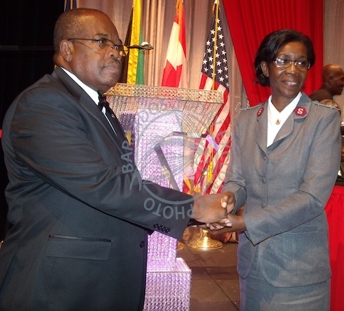 Outgoing president of the Kiwanis Club of Bridgetown, Kenneth Knight (L), presents the Kiwanis Citizen of the Year award to the Salvation Army's divisional leader, Major Rosemarie Brown, who received it on behalf of the organisation.