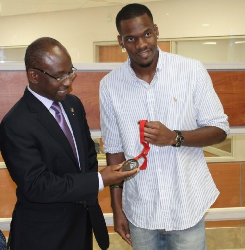 Minister of Sports Stephen Lashley admiring Shane Brathwaite's bronze medal which he won at the Commonwealth Games in Glasgow, Scotland.