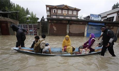 Residents leave a flooded neighborhood on a boat in Srinagar, India, today.