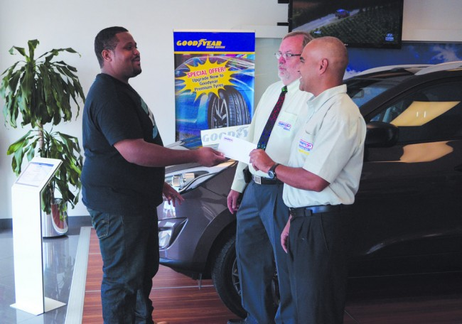 BADD's Michael Carter (left) receiving the sponsor's cheque from Courtesy Garage's Mark Wilson at the company's showroom, while Ian Proverbs looks on.