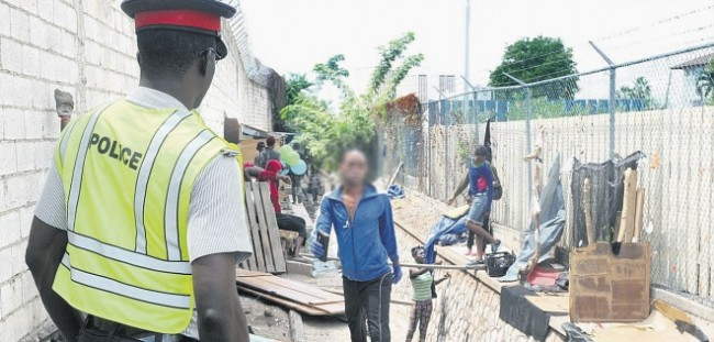 Police on operation in the Shoe Maker Gully in New Kingston, yesterday.