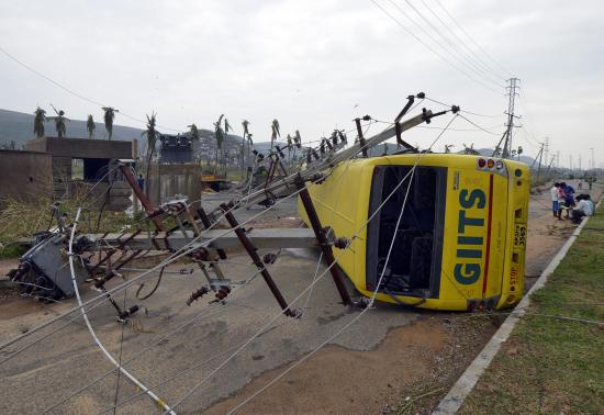 Power lines and a passenger bus are seen after being damaged by strong winds caused by Cyclone Hudhud in the southern Indian city of Visakhapatnam
