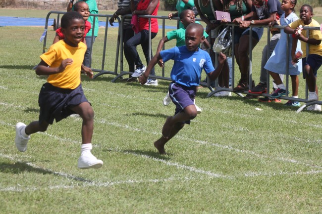 Azevier Callender of Yelow House was busy sprinting his way to the finish line while David Simmons of blue looks across.