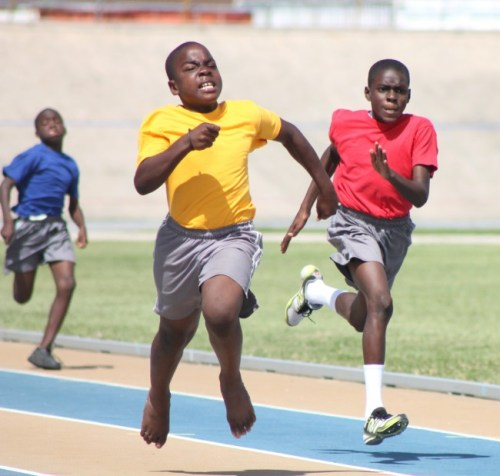 Jamario St Hill of Yellow House  managed to hold off Romario Roach of Red House in the under-13 boys 100m during St Giles Primary's sports day.