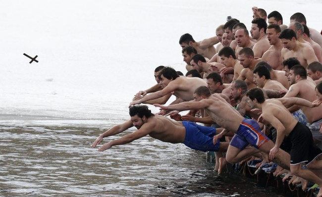 Men jump into the waters of a lake in an attempt to grab a wooden cross on Epiphany Day in Sofia