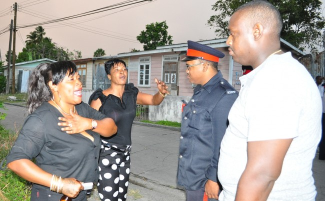 They had not too long returned home from a friend's funeral when residents of Chapman Lane, The City heard gunshots ring out                 in their neighbourhood. Their initial fear turned to outrage when they realized lawmen were discharging weapons in a neighbourhood where children were at play. Here, two of the angry residents confront officers on the scene of the incident in which   a young man being pursued by police was shot.