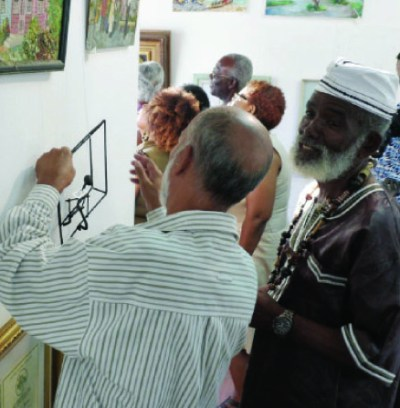 President of the Barbados Arts Council Ahmad Boodoo admiring a painting with Fielding Babb.