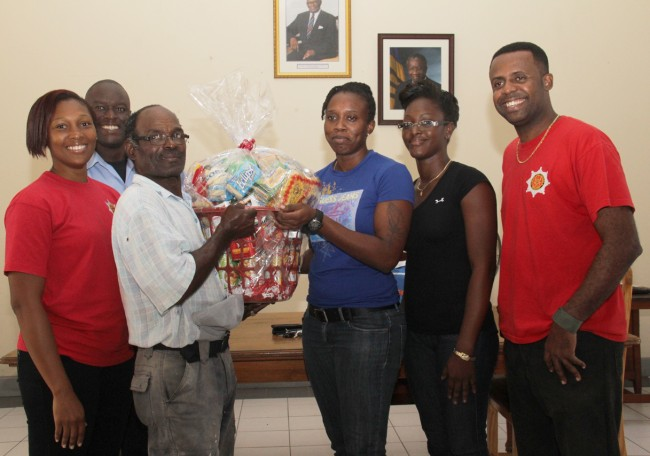 Robert Howard (left) receives his basket of goodies from fire officer Reshelle Howard who rallied her colleagues to lend a helping hand.