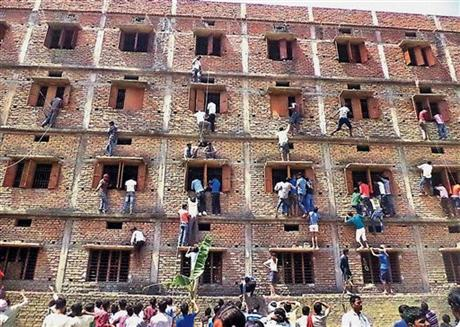In this photo taken Wednesday, Indians climb the wall of a building to help students appearing in an examination in Hajipur,  in the eastern Indian state of Bihar.