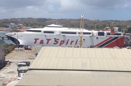 Vehicles queuing to go aboard the T&T Spirit, as workers attempt to fix the ramp.