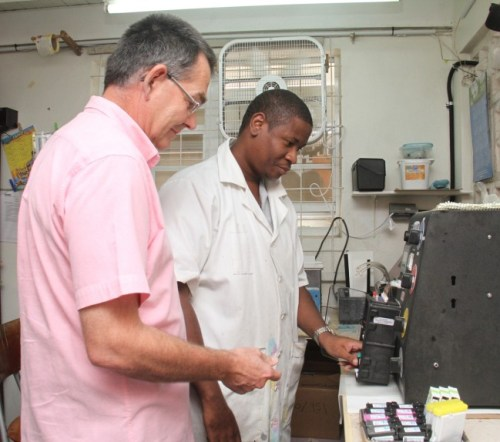 Inktech's technician Dan Dreo Alleyne (right) preparing one of the cartridges for refilling as managing director Tom Fountain looks on.