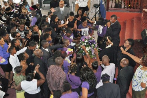Reverend Dr David Durant  (top right) praying over the casket of Lamar Brathwaite with family and friends.