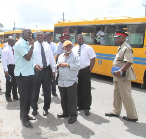 Minister of Transport and Works Michael Lashley with members of the Royal Barbados Police Force during a tour of the River Terminal today.