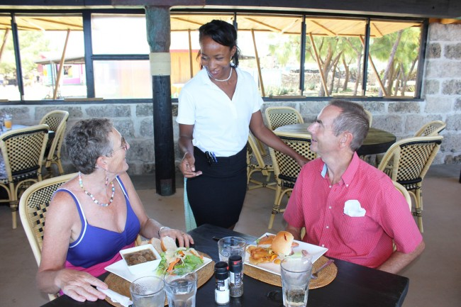 English visitors Elizabeth Harvey (left) and Robert Harvey,  who have made 38 visits to Barbados so far, being made comfortable by head waitress Angela Haynes at today's lunch.