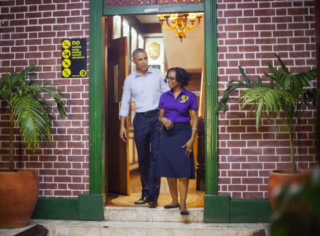 U.S. President Barack Obama walks outside with tour guide Natasha Clark, during his unannounced visit to the Bob Marley Museum in Kingston, Jamaica, Wednesday, April 8, 2015. (AP Photo/Pablo Martinez Monsivais)