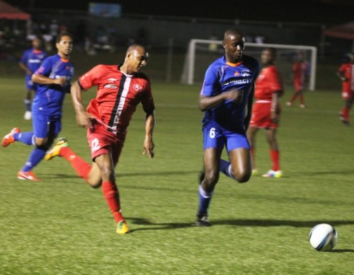 Brittons Hill's goal scorer Mustafa Haqq sprints to the ball before Paradise defender Zico Phillips.