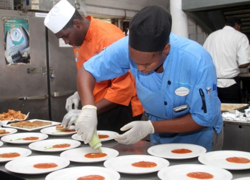 Chefs Andre Nurse (left) and Stephanie Sears putting the finishing touches on these meals.