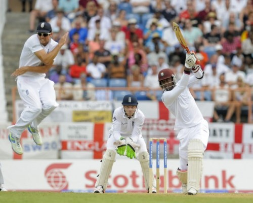 England captain Alastair Cook (left) gets out of the way of a powerful drive from Marlon Samuels.