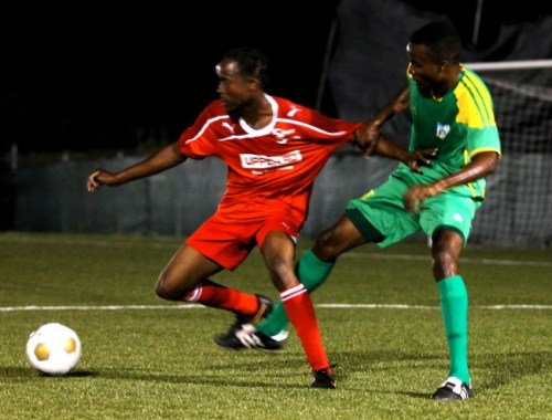 Goal scorer Mario Kinch (left) of Silver Sands played well and oftentimes was held back from making runs on the BDFSP's goal, such as this occasion when Decarlo Jemmott tried to hinder his progress.