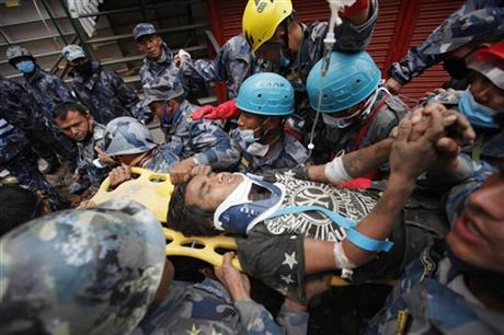 Pemba Tamang being carried on a stretcher after being rescued by Nepalese policemen and American rescue workers from a building that collapsed five days ago in Kathmandu, Nepal.