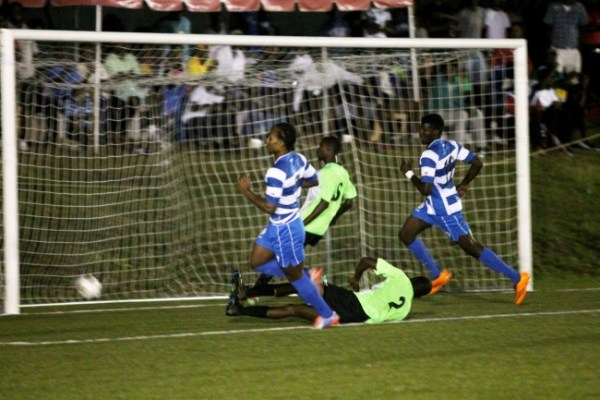 Romano Snagg (left, in blue & white) scoring one of his three goals.
