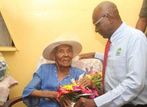 UDC director Derek Alleyne presenting Aunt Berths with a bouquet.