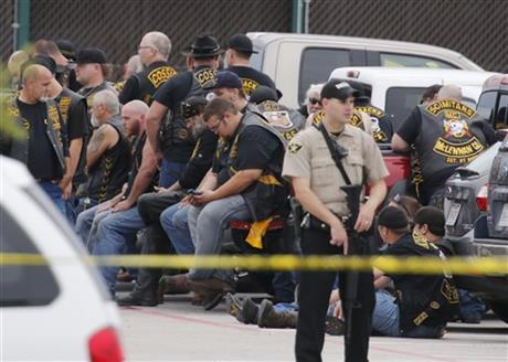 A McLennan County deputy standing  guard near a group of bikers in the parking lot of a Twin Peaks restaurant yesterday.
