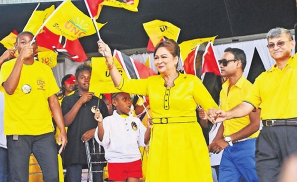 Prime Minister Kamla Persad-Bissessar, flanked on the right  by husband Dr Gregory Bissessar, waves the national flag as she    walks onstage for the People's Partnership's fifth anniversary rally.